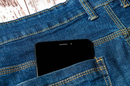 black smartphone sticking out of his jeans pocket