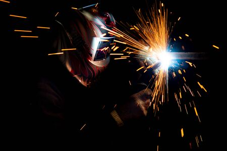 male welder in a mask performing metal welding. photo in dark colors. sparks flying.