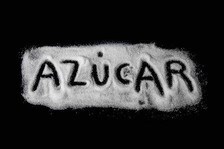 word sugar written in Spanish of white granulated sugar and powdered sugar on dark stone background, top view
