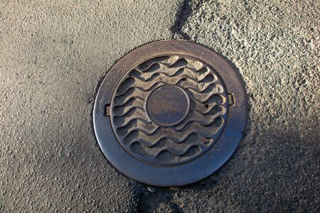 Sewer manhole on the urban asphalt road. Closeup photo Stok Fotoğraf - 128308006