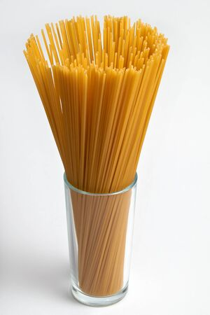 spaghetti in a glass on white background