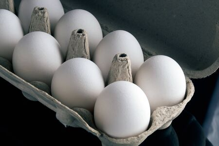fresh eggs in the opened box on black background