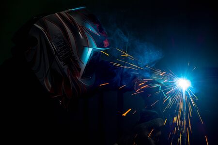 male welder in a mask performing metal welding. photo in dark colors. sparks flying. Stok Fotoğraf