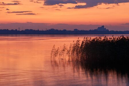 lake and city on the background of a colorful sunset Stok Fotoğraf