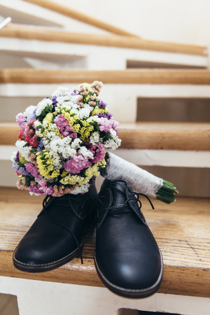 Wedding bouquet on the grooms shoes which stand on the stairs