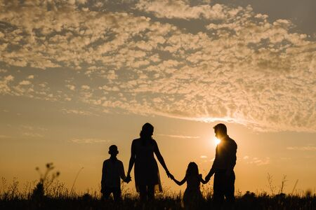 Family on sunset background. Hold hands and look at the sun
