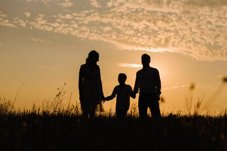 Family on sunset background. Silhouette of family at sunset sun and against the sky with clouds holding hands of son