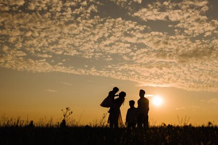 Family on sunset background. Silhouette of mother holding daughter in her arms, and dad next to her son against the sky with clouds