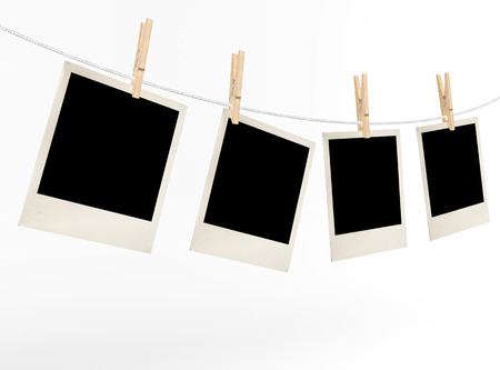 Blank photos on a rope weighing on a white background
