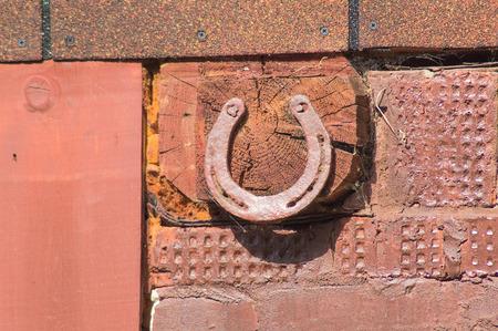 Old rusty horseshoe nailed to the log photo