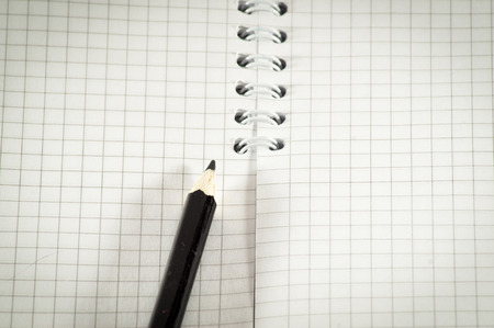 Black pencil on a background of the disclosed notepad close-up. photo