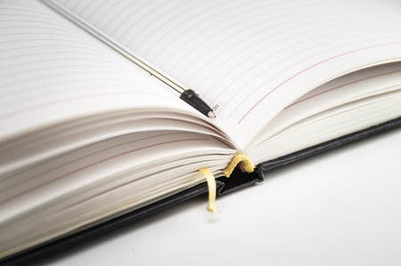 Open notebook with bookmark and pen closeup on a white background. Photo. Imagens