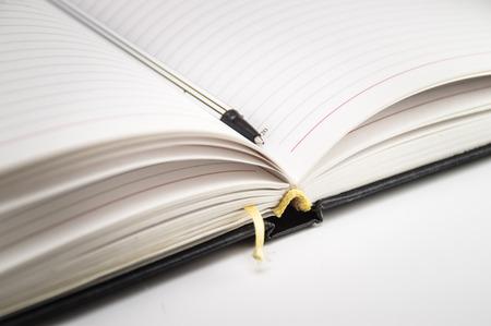 Open notitieboekje met referentie en penclose-up op een witte achtergrond. Foto. Stockfoto