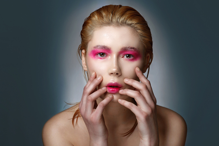soulful eyes: Studio portrait of young blonde girl with wet hair and pink bright makeup Stock Photo