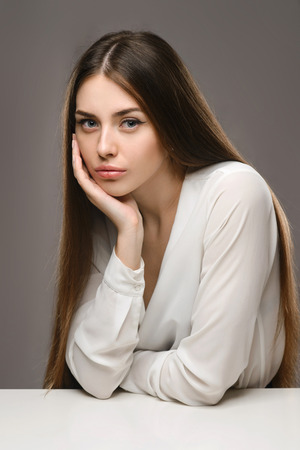Beauty portrait young girl sitting at the white table in white blouse and black skirt on gray background in bussiness style