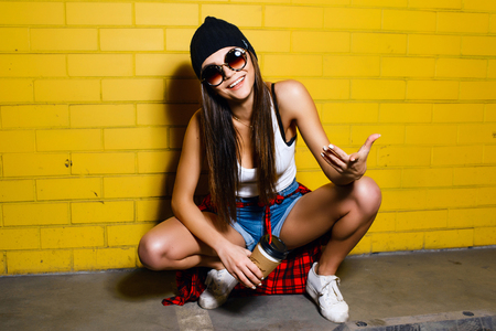 plaid shirt: Beautiful young sexy hipster girl drink coffee and sitting near urban yellow wall background in sunglasses, red plaid shirt, shorts, hat. Stock Photo