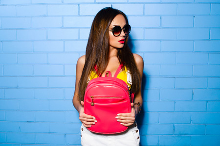 jumpsuit: Beautiful young sexy hipster girl posing and smiling near urban blue wall background in yellow swimsuit, white jumpsuit, sneakers, sunglasses, pink backpack. Stock Photo