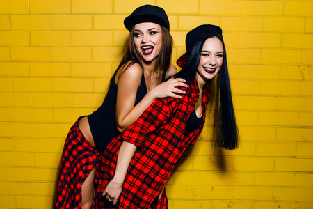 girls having fun: Two young happy hipster girls having fun, smiling, laughing, jumping, walking  near urban yellow wall background, summer relax concept