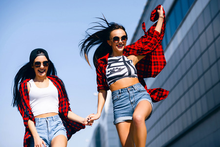 niñas sonriendo: Two young happy hipster girls in sunglasses having fun, smiling, laughing, jumping, walking outdoor on the street, summer relax concept Foto de archivo