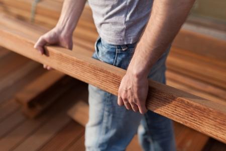 Construction worker holding wooden beam Standard-Bild