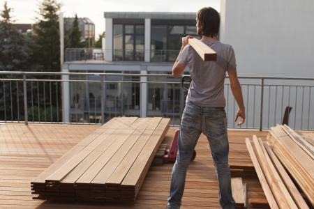 floorboards: Trabajador de la construcci�n. Suelo de madera. Viga de madera. Foto de archivo