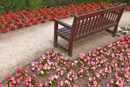 garden bench: Blooming flowers  Gravel Walkway and Wooden Bench Stock Photo