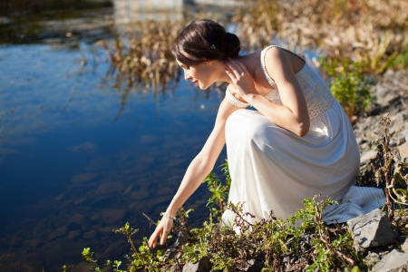 Young woman sitting by water and looking at her reflection Standard-Bild