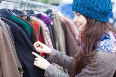 경향: 매력적인 여자는 벼룩 시장에서 옷을 선택.