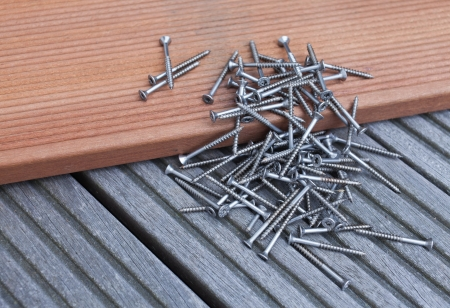 Pile of screws on a floorboard Archivio Fotografico