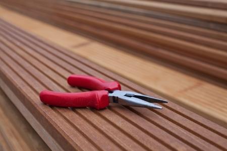 Needle-nose pliers on a floorboard Archivio Fotografico