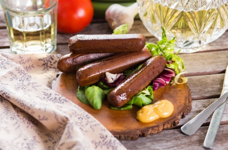 Grilled sausages served on wooden plate
