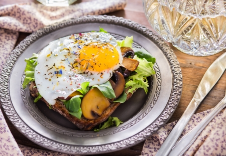 Fried egg with champignons, lettuce on the toast