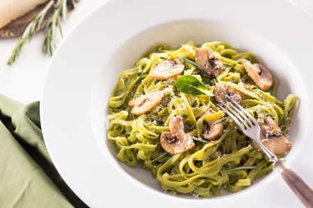 Tagliatelle pasta with pesto on white plate Standard-Bild