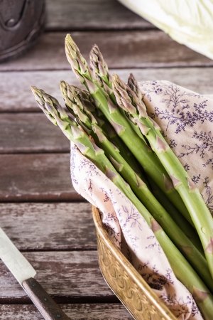 Bunch of fresh green asparagus spears on a rustic vintage table