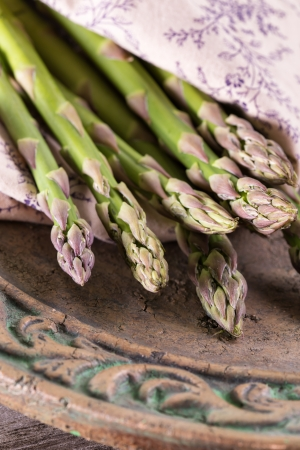 Bunch of fresh green asparagus spears on a rustic vintage plate Standard-Bild