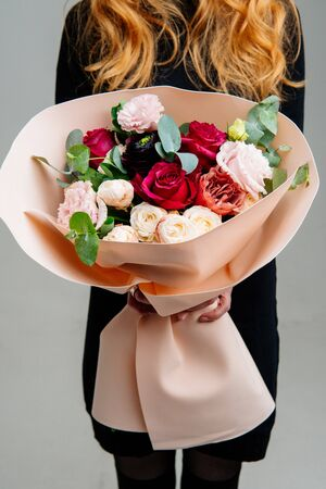 Bouquet of flowers in peach foamiran package in the hands of red-haired girl florist on light background. Rose, eustoma, ranunculus, eucalyptus.