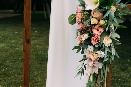 Fragment of wooden arch for the wedding ceremony, decorated cloth, flowers and greenery