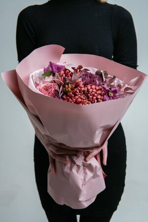 Bouquet of flowers in pink package in the hands of a woman florist on a light background. Rosa, carnation, chrysanthemum, cotinus, pistach, brunia, clematis. Standard-Bild