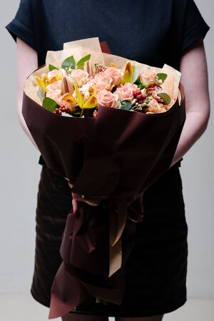Bouquet of flowers in burgundy package in the hands of a woman florist. Rosa, orchid, lily, brunia, carnation, eucalyptus.