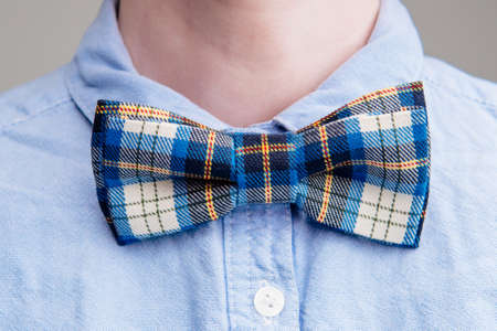 Blue scottish cage bow tie on a woman's neck in blue shirt on light background.