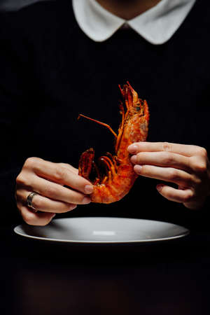 fried lobster on a white plate in the hands of a woman on a black background