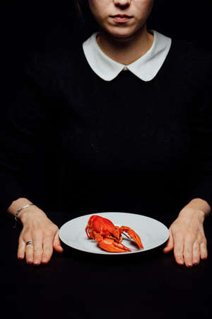girl boiled crayfish in the hands on a white plate on a black background Stock fotó