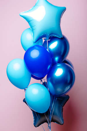 Composition of dark blue, blue, transparent helium balloons and two sapphirine star on a pink background.