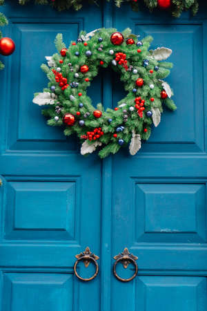 Christmas wreath of fir branches on a blue wooden door and a garland of fir branches. Stockfoto