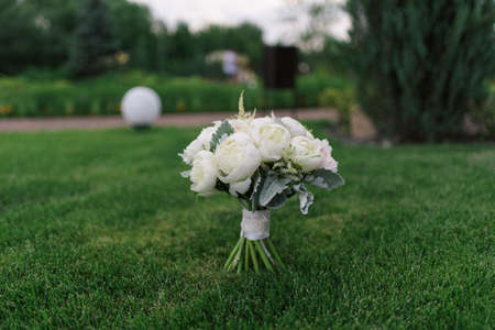 Wedding floral bouquet of white peonies and roses on the green background