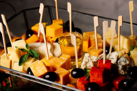 Gourmet cheese platter with olives, honey for party with friends