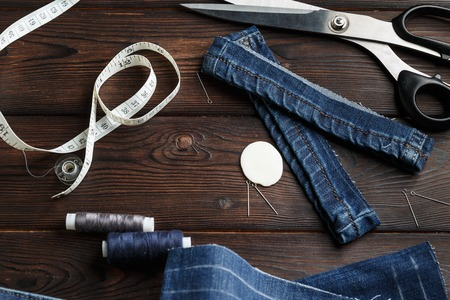 trouser legs: Jeans with dressmaking sewing utensils needlework on the dark old wood background Stock Photo