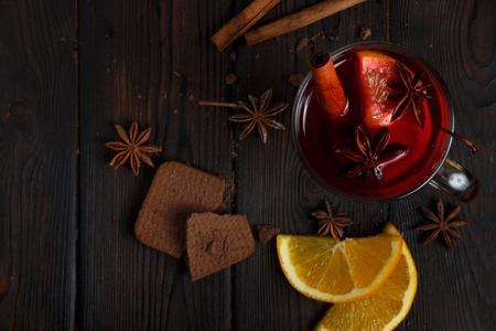 Mulled wine with delicious orange and spic on the dark old wood background Stock Photo
