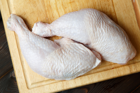 poultry: Fresh raw chicken legs on wooden board on the wooden background