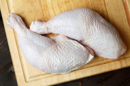 aves de corral: muslos de pollo sin procesar frescas en la tabla de madera en el fondo de madera
